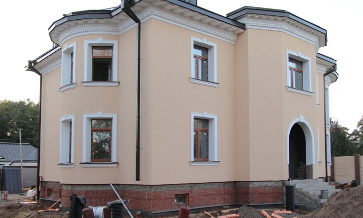 фасадный лепной декор из полимербетона на доме с бежевой штукатуркой