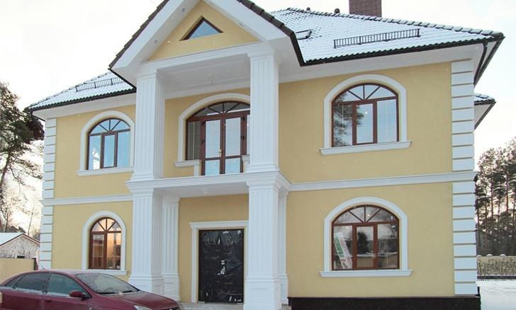 Дом с желтой штукатуркой и декоративными элементами из пенополистирола