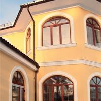 Венчающий и межэтажный карниз на эркере дома с желтой штукатуркой