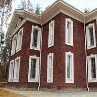 Вид на дом с клинкерной плиткой и декором на окна из полимербетона, оформление подшива кровли