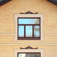 Наличники окон с прорезными орнаментами и межэтажными тягами