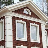 Фронтон дома с угловыми декоративными элементами и оформление окон наличником с замковым камнем