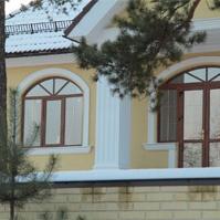 Наличники и подоконники белого цвета на фасаде дома