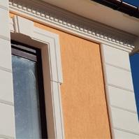 Подкровельный карниз из полимербетона на фасаде с желтой штукатуркой, рустованные камни