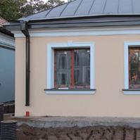 Наличники и подоконники белого цвета на окнах дома из декоративной штукатурки