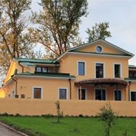 декоративные наличники на окнах усадьбы с желтой штукатуркой