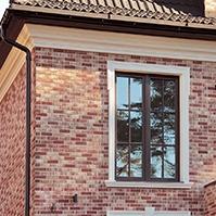 Карниз под крышей на фасаде и окно с наличником
