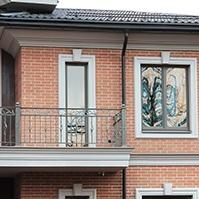 наличники по периметру окон с замковыми камнями, карниз балкона