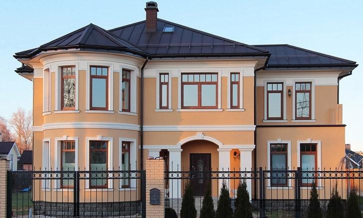 Фасадные декоративные изделия из полимербетона на доме с персиковой штукатуркой, обрамление окон
