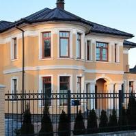 Дом с персиковой штукатуркой и оформлением окон наличниками и подоконным карнизом