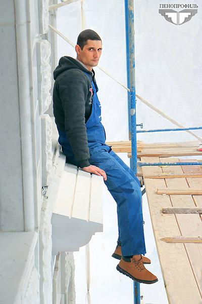 Человек сидит на фасадном декоре